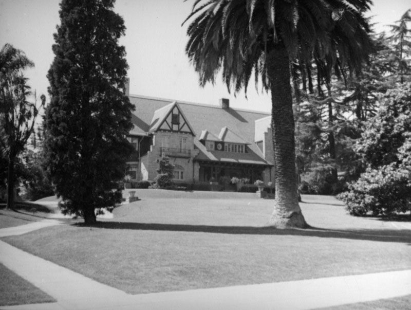 A large house with trees and a lawn in front of it.