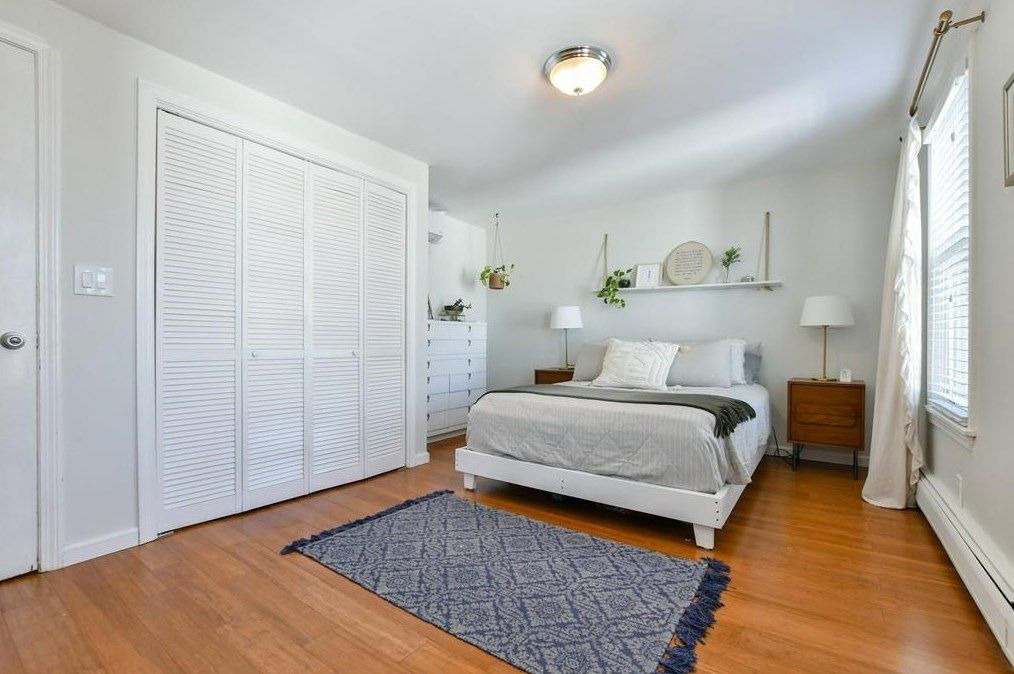 A bedroom with a bed and a long, closed closet.