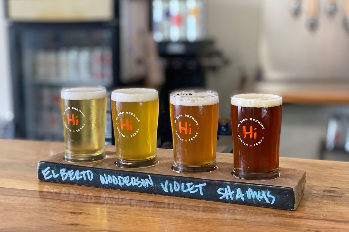 Four beers in pint glasses on a board with the names written in chalk