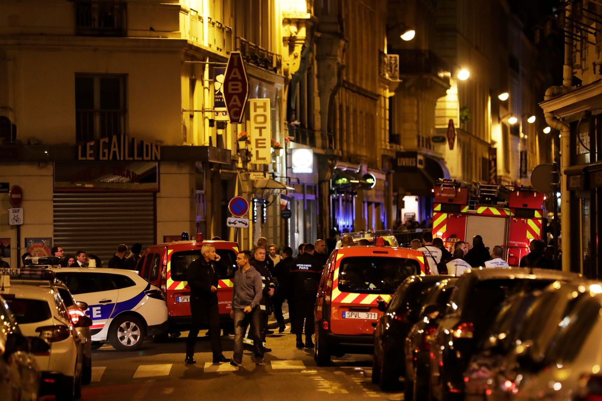 Policemen and emergency service members stand in a blocked street in Paris after one person was killed and several injured by a man armed with a knife, who was shot dead by police in Paris on May 12, 2018.