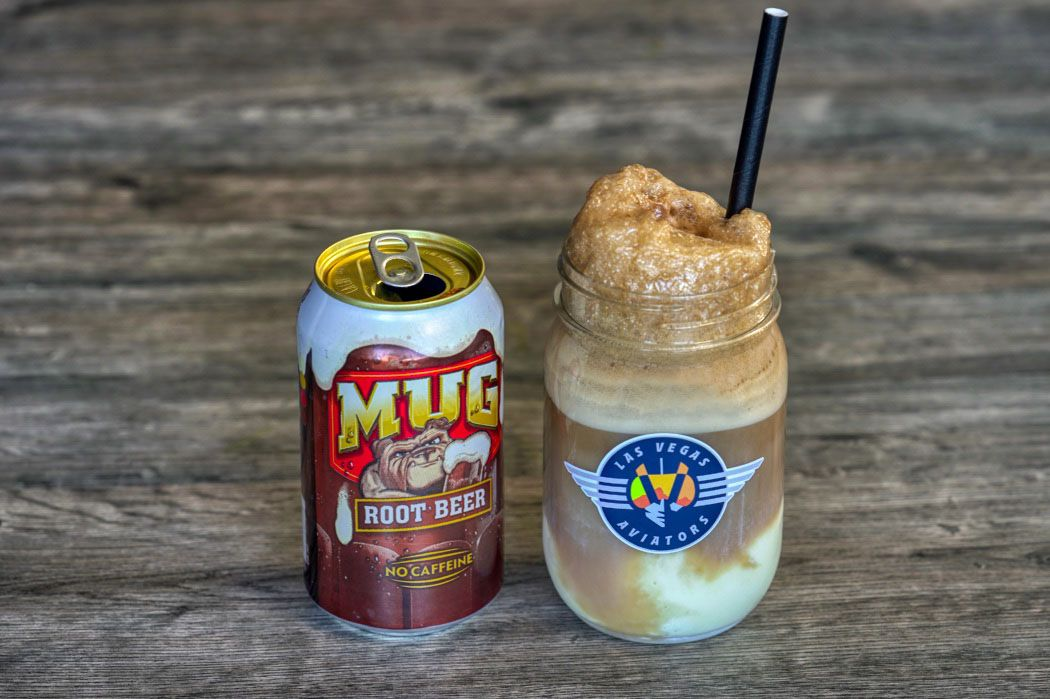 A root beer float in a Mason jar next to a can of root beer