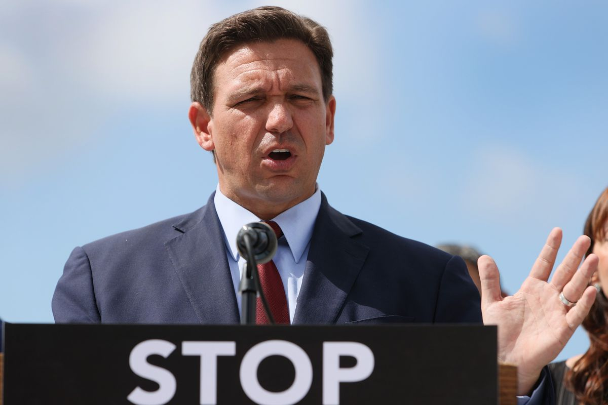 """Florida Gov. Ron DeSantis speaks during a press conference held at the Florida National Guard Robert A. Ballard Armory on June 7, 2021 in Miami, Florida. The word """"stop"""" is visible on the lectern."""