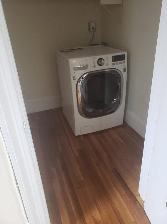 A closet empty except for a square washer-dryer machine.
