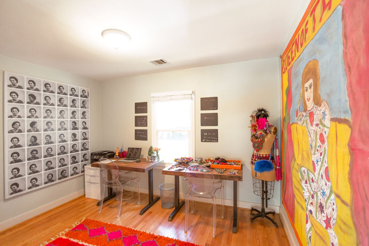 """A room with large wall-hanging art, including a vintage circus banner advertising the """"Queen of Tattoo."""""""