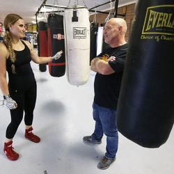 Boxer Whitney Gomez talks with trainer Nick Butterfield at Fullmer Brothers Boxing Gym in South Jordan on Wednesday, June 7, 2017.
