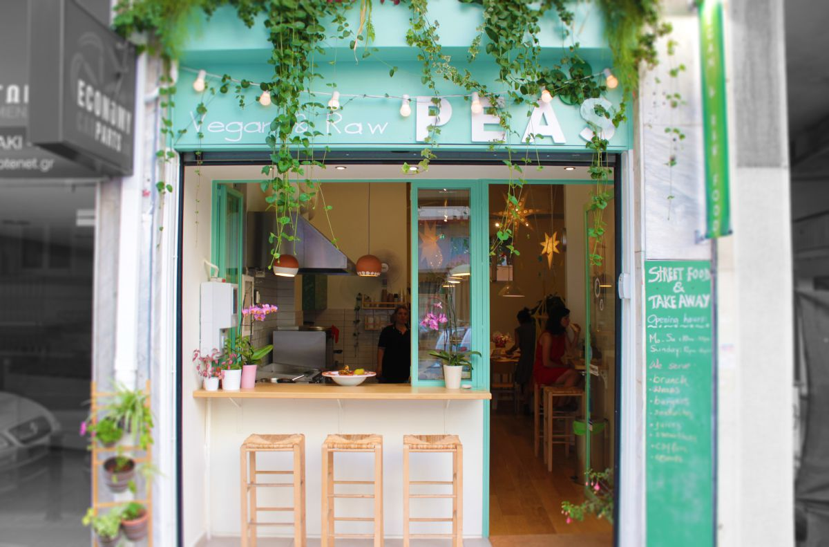 A small shop exterior covered in plants. The door and wide window are open. Stools are set on the outside of a counter on the window ledge