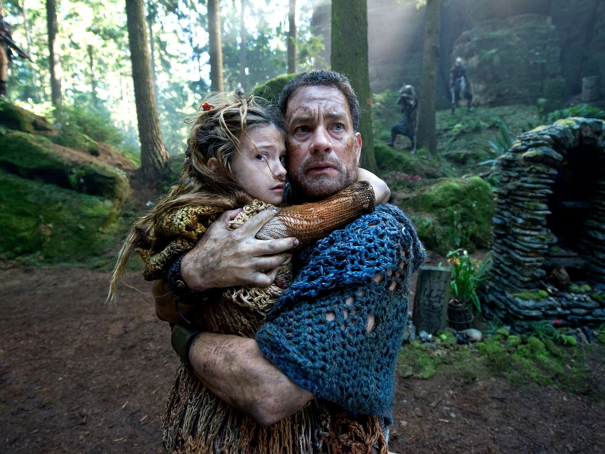 Zachry (Tom Hanks) clutching a child to him while surrounded by marauders in Cloud Atlas.
