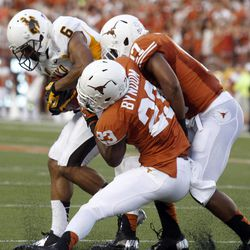 Wyoming's Robert Herron (6) works his way free from Texas defenders Carrington Byndom (23) and Adrian Phillips during the first quarter of an NCAA college football game, Saturday, Sept. 1, 2012, in Austin, Texas.