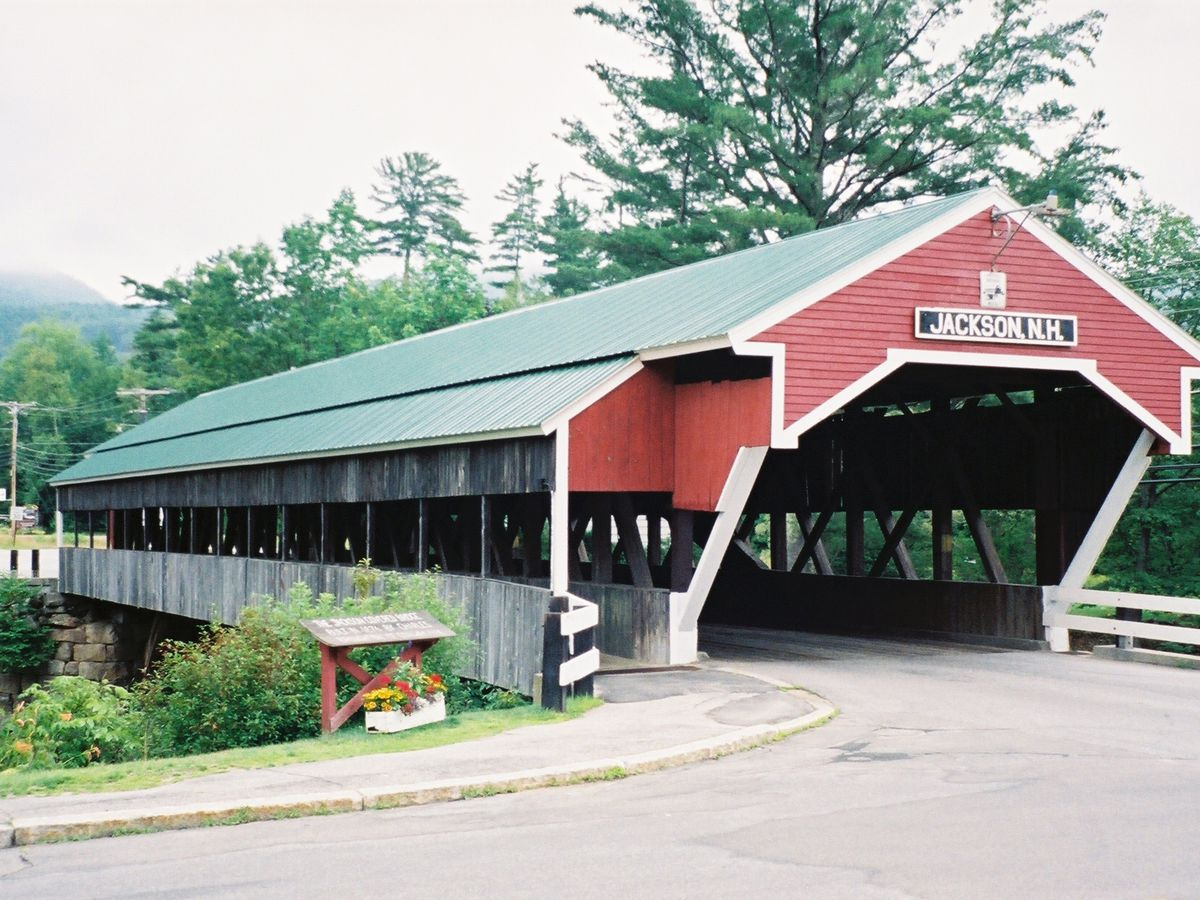 A red covered bridge with a light grey roof. In the foreground is a path leading to the bridge. In the background are trees.