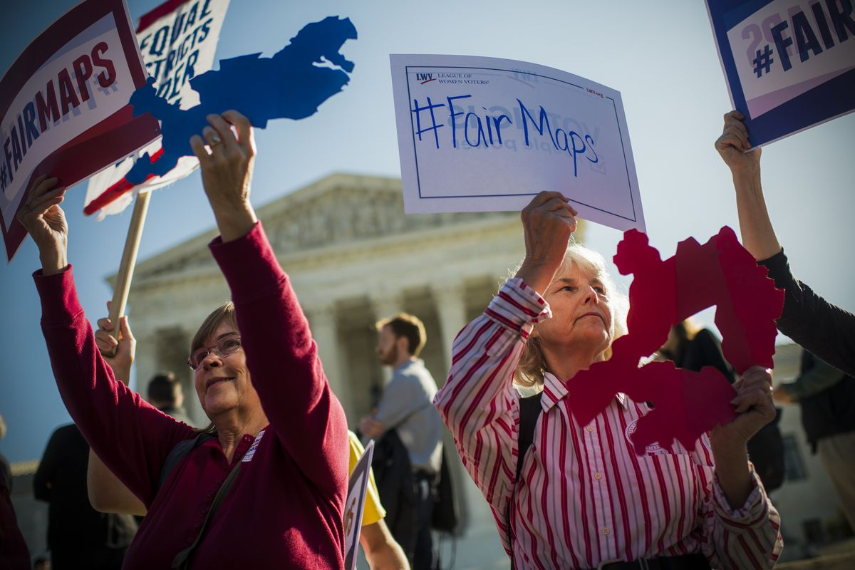 Shirley Connuck (right) of Falls Church, Va., holds up a sign outlining a district in Texas, as the Supreme Court hears a case on partisan gerrymandering by state legislatures on October 3, 2017.