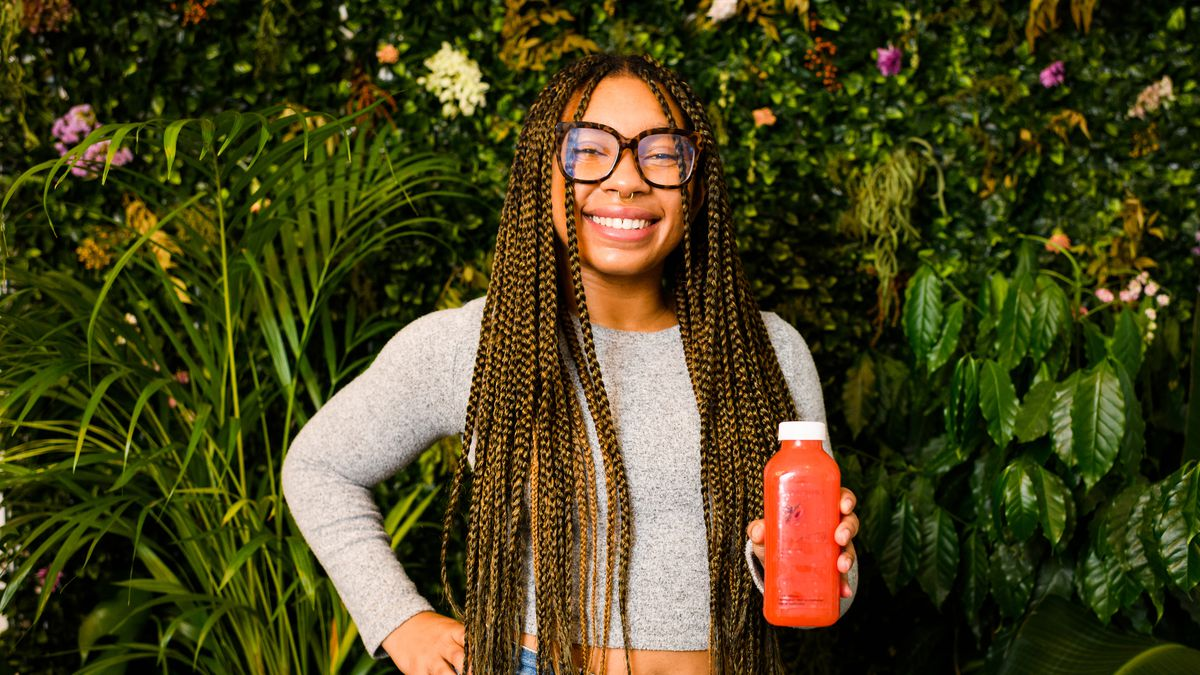 A woman with long dreads, glasses, and high-waisted jeans stands in front of a plant wall with a bottle of juice in her hand