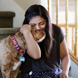 Stephanie Pesantes, who traveled to Washington, D.C., to meet with Michelle Obama, plays with the family dog, Teddy, in Salt Lake City, Tuesday, July 28, 2015.