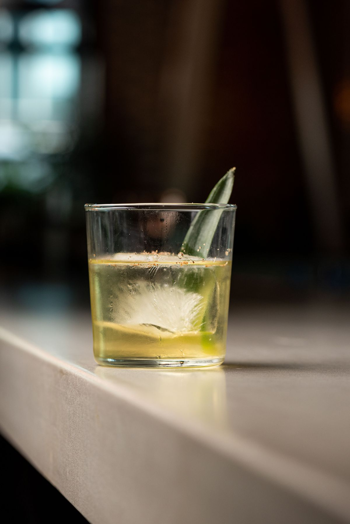 A side view of a semi-clear cocktail with a big square rock of ice.