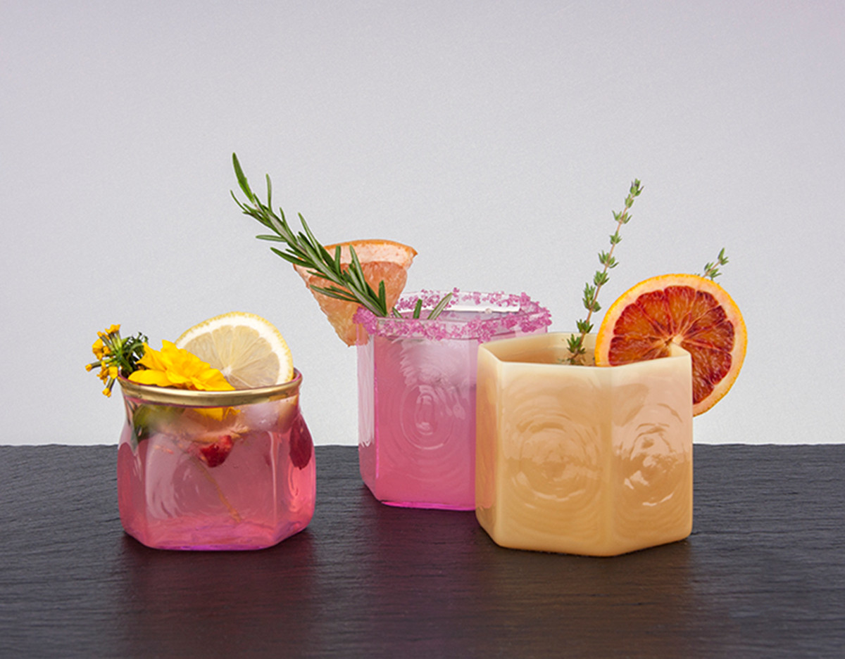 Three handmade glasses designed by artisans in Los Angeles. There is a pink glass, an orange glass, and a clear glass. The pink and orange glass have a hexagonal shape. Each glass has a drink in it with fruit and plant garnishes.