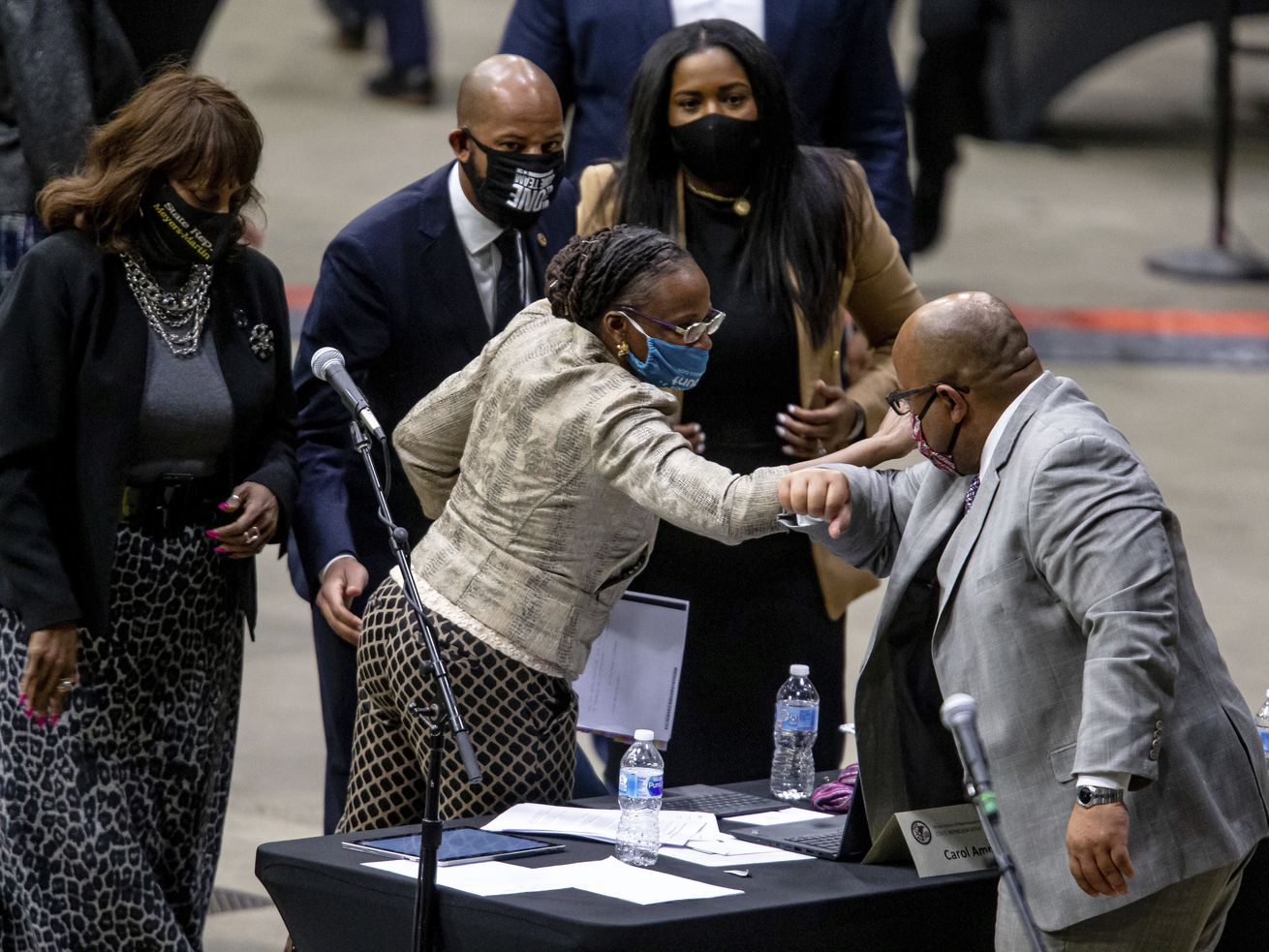 State Rep. Carol Ammons, D-Urbana, gets an elbow bump from state Rep. André Thapedi, D-Chicago, after passage of the Illinois Black Caucus' Education Pillar on Monday.