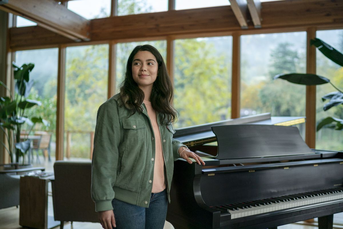 a girl stands next to a grand piano
