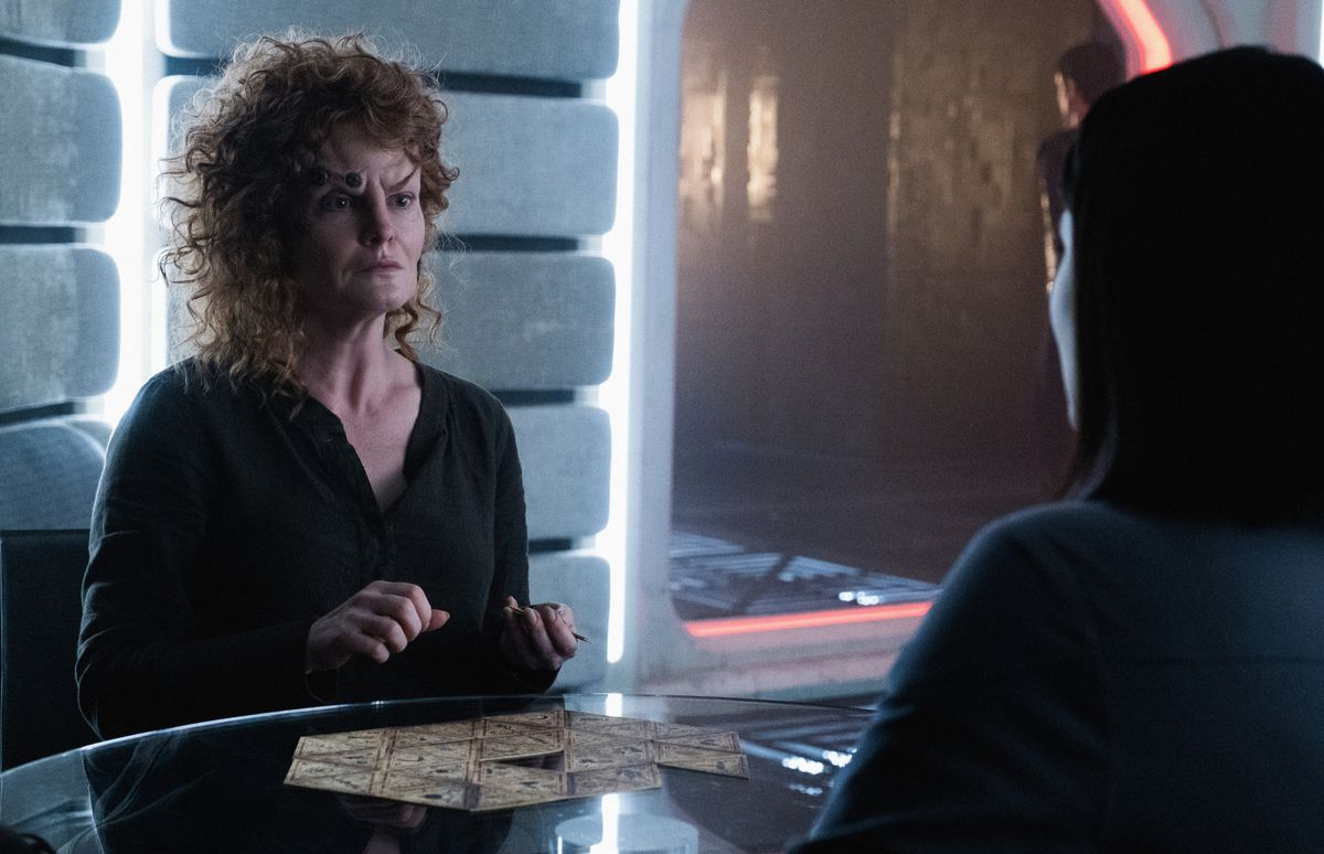 A wild-haired Romulan with Borg facial implants lays out a series of triangular Tarot-like patterned cards as if assembling a puzzle.