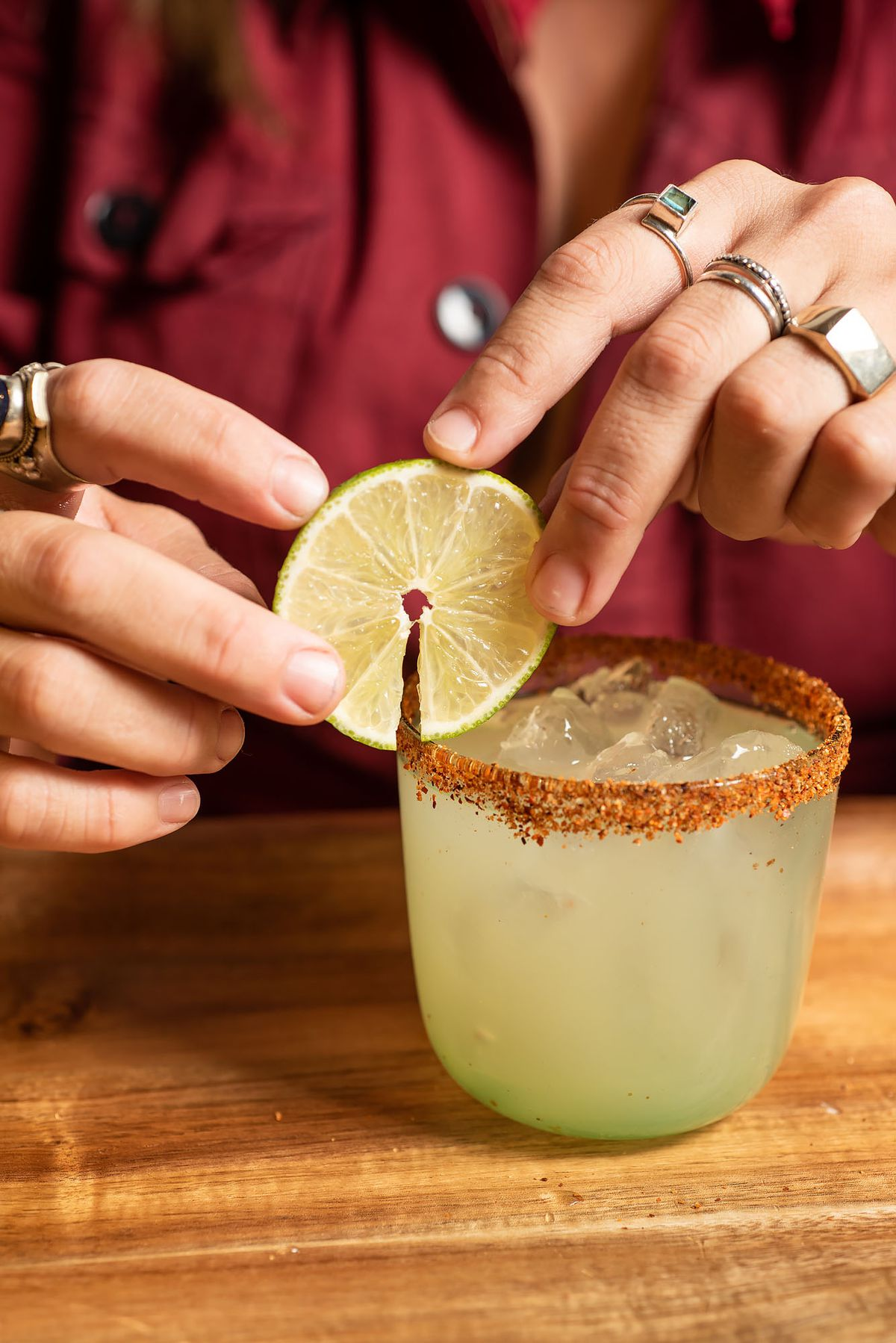 Gavaldon uses two hands to add a circle lime garnish to a lime-green cocktail.