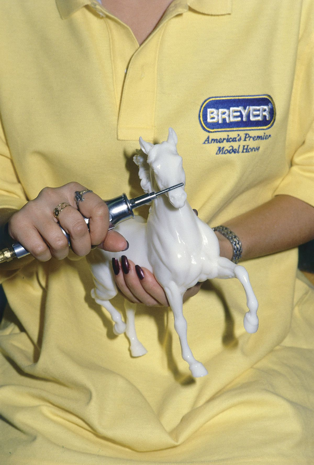 a Breyer technician fine sculpting a molded horse