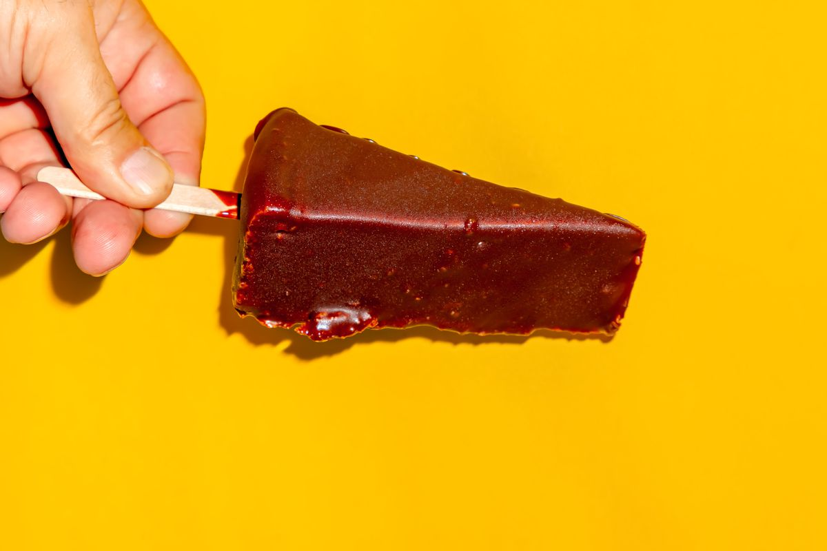 A hand holding a chocolate-dipped cheese on a stick against a yellow background