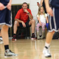 Larry Krystkowiak, head coach for the Utah Runnin' Utes, watches, along with his daughter, Finley, as his sons play in a Team Camp basketball tournament at the University of Utah in Salt Lake City on Friday, June 12, 2015.