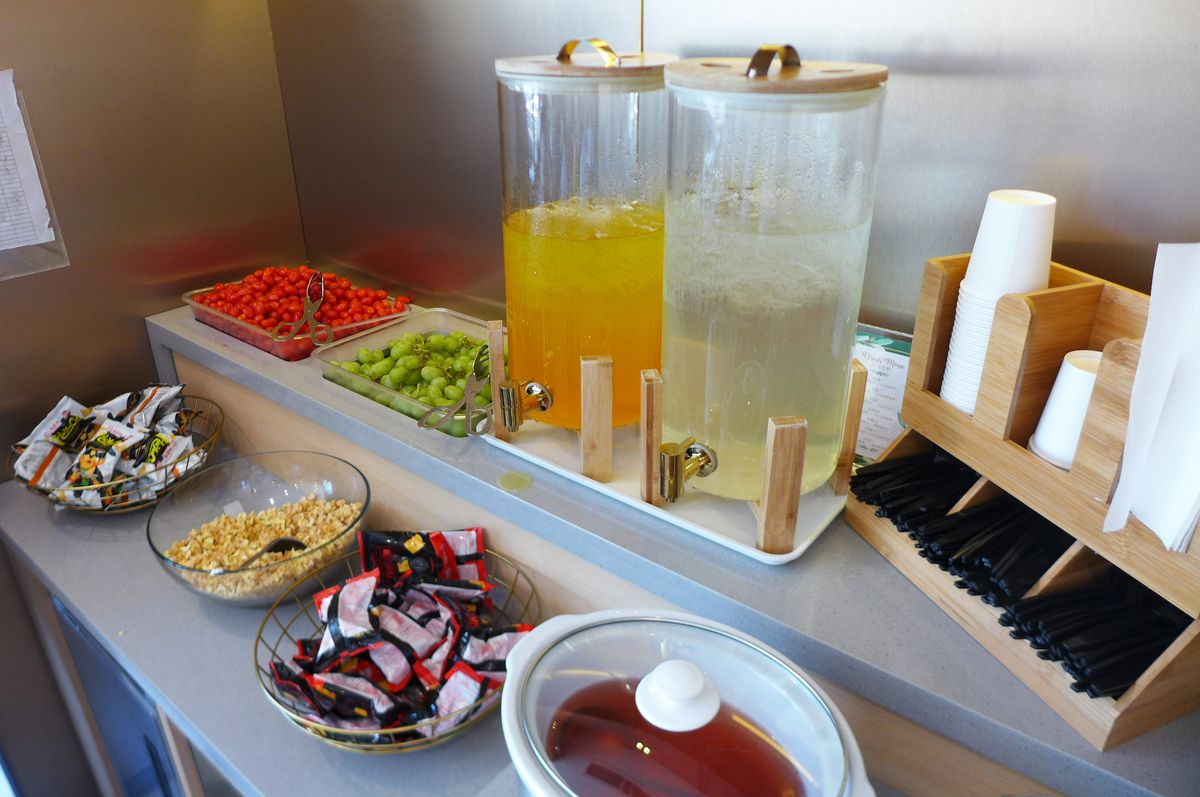 Two tall help yourself beverage cylinders and several packages of snacks are provided...