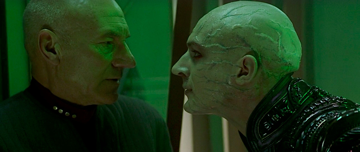 Patrick Stewart as Jean-Luc Picard faces his bald, rubber-suited, veiny-faced clone Shinzon (played by Tom Hardy) under dark green lights in Star Trek: Nemesis.