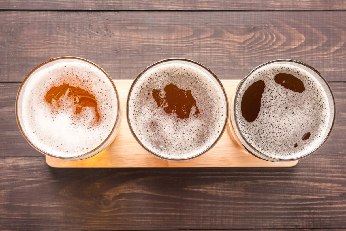 An aerial photograph of three glasses of beer, which increase in darkness from left to right