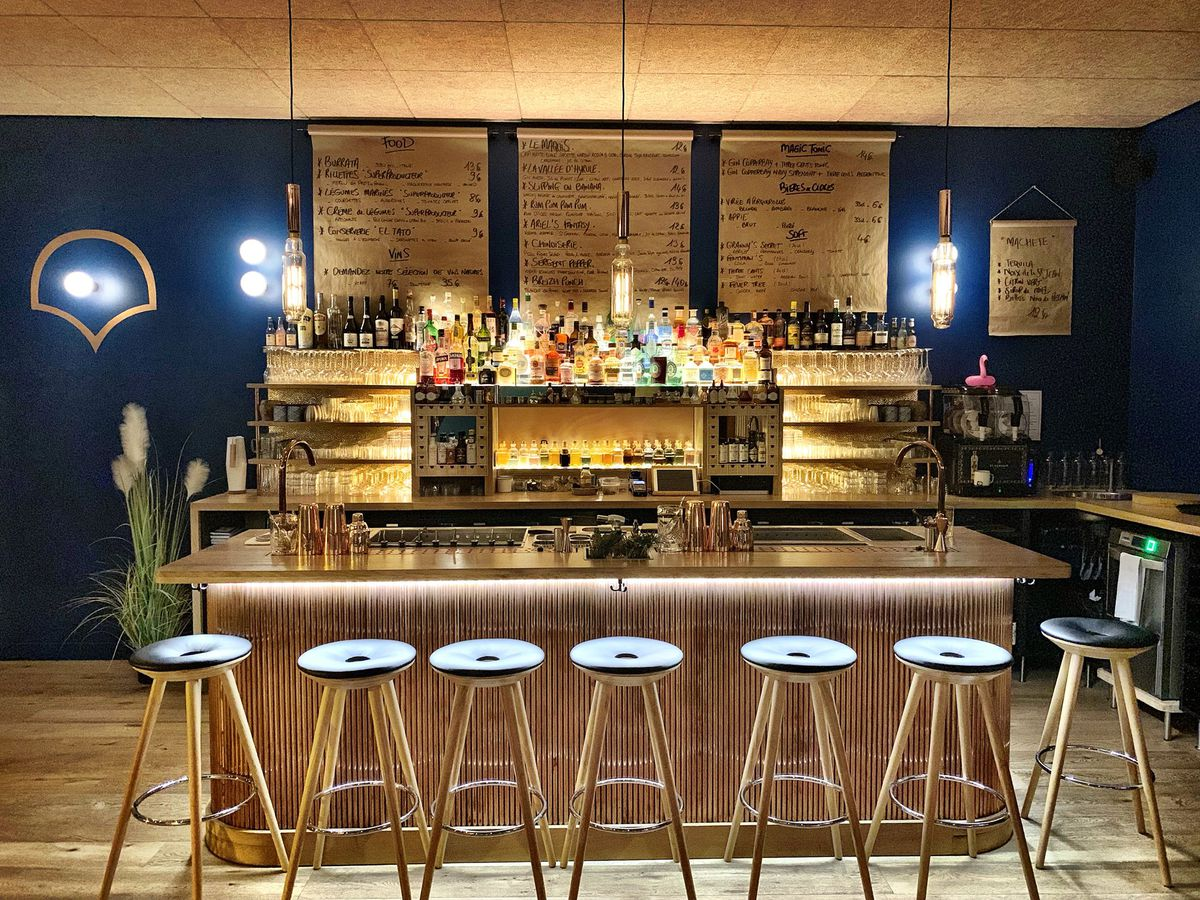 Empty stools sit at a gilded, lit bar against a deep blue painted wall, with menus written out on butcher paper rollers hung on the back wall, bottles on the illuminated back bar, and gold fixtures set on a wooden bar top