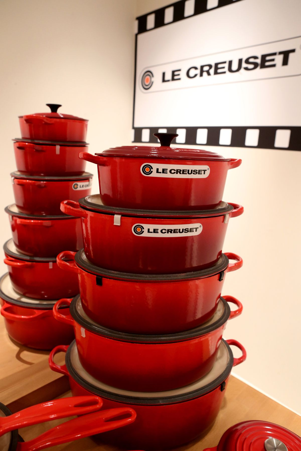 Stack of red Le Creuset Dutch ovens of different sizes
