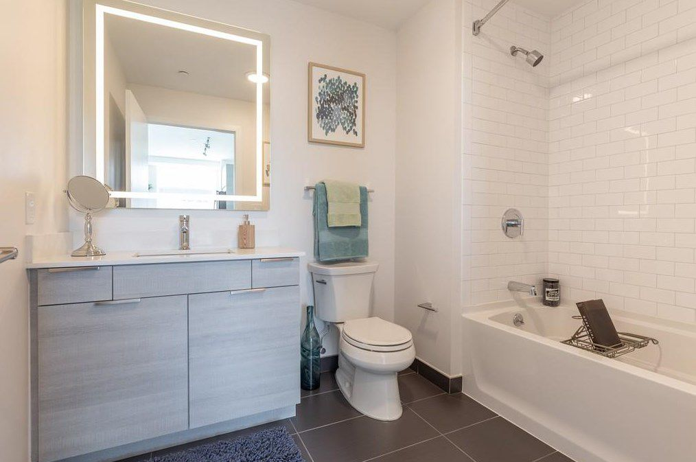 A newer bathroom with the curtain pulled back on the tub.