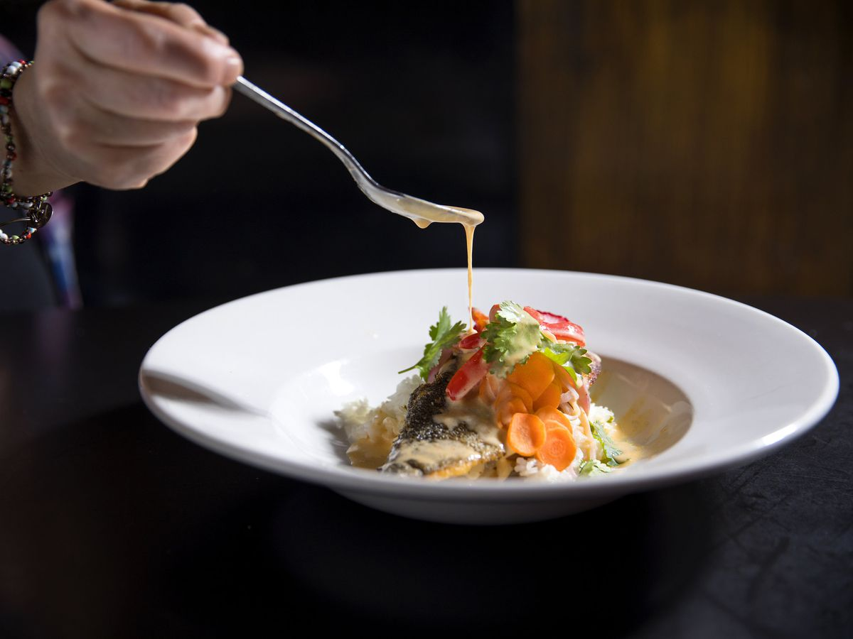 A hand drizzles sauce with a spoon on a fish under a pile of cooked vegetables