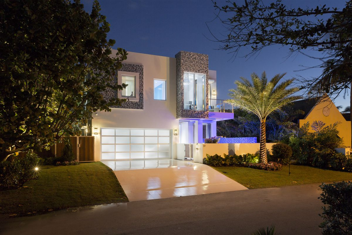 Modern micro mansion in Florida with neon lighting, multiple stories, and a garage door