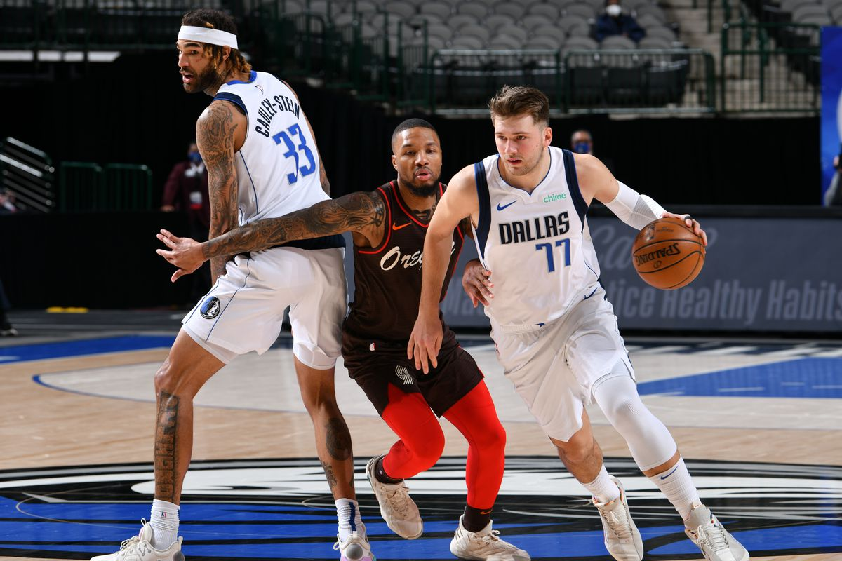 Luka Doncic of the Dallas Mavericks drives to the basket while Damian Lillard of the Portland Trail Blazers plays defense during the game on February 14, 2021 at the American Airlines Center in Dallas, Texas.