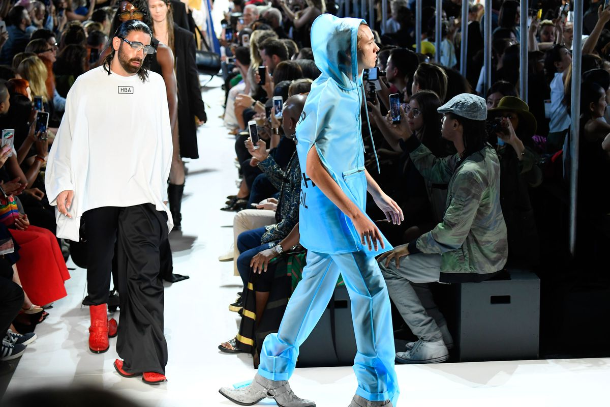 A model walks the runway in a translucent blue hoodie and pants, with boots that have an extra toe extending backward, from the heel.
