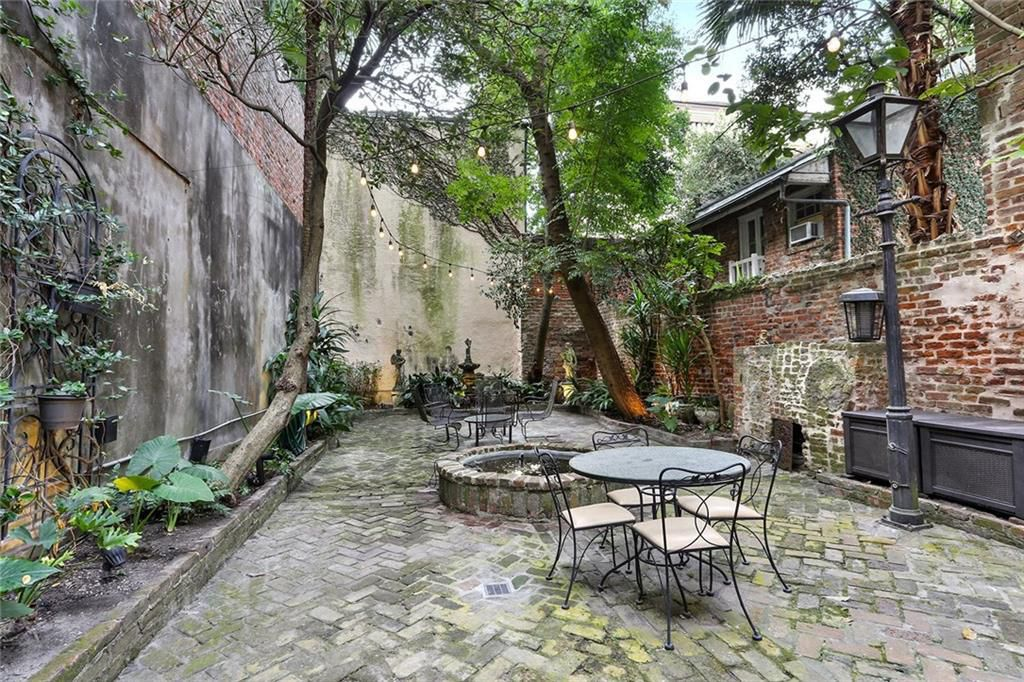 A brick-lined courtyard is shaded by two leaning trees standing above a fire pit in the center with a small table and chairs in front of it.