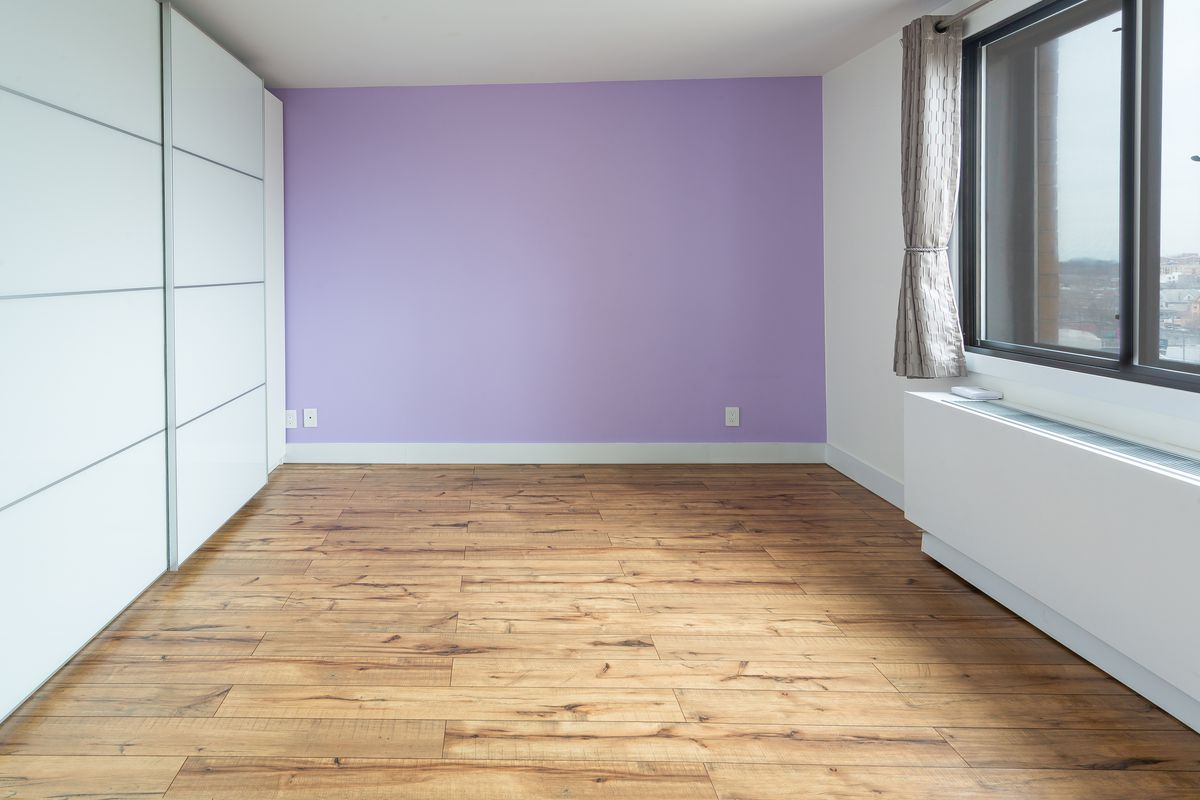 A bedroom with hardwood floors, a purple wall, and a large window.
