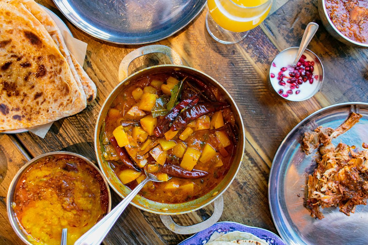 A metal bowl of spiced potatoes surrounded by other Indian dishes like paratha and dal.
