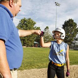 Brad Thomas, left, who has been coaching his daughter's accelerated softball team for the past five years, fist-bumps Grace Humes during a scrimmage at Dewey Bluth Park in Sandy, Utah, Thursday, June 9, 2016.