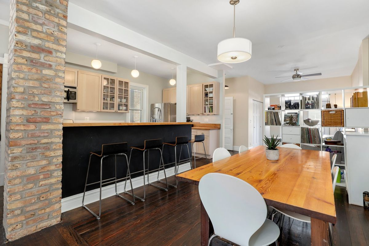 The open kitchen and dining room. There is a large wood table and breakfast bar with stools. Thee kitchen features light wood cabinets and globe glass light shades.