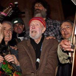 """Activist musician Pete Seeger, 92, center, sings before a crowd of nearly a thousand demonstrators sympathetic to the Occupy Wall Street protests at a brief acoustic concert in Columbus Circle, Saturday, Oct. 22, 2011, in New York. The demonstrators marched down Broadway singing """"This Little Light of Mine"""" and other folk and gospel songs while ad-libbing lines about corporate greed and social justice."""