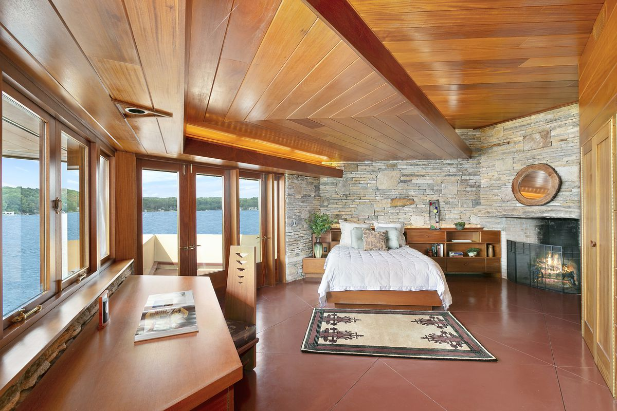 A bedroom area with a bed, table, chair, fireplace, stone wall, and wooden ceiling. There are floor to ceiling windows overlooking a body of water.