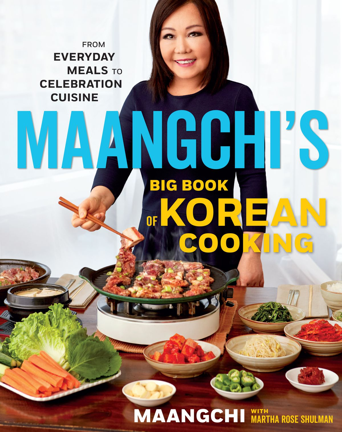 """Cover of """"Maangchi's Big Book of Korean Cooking: From Everyday Meals to Celebration Cuisine"""" cookbook, with Maangchi standing over a steaming pot and smiling at the camera"""