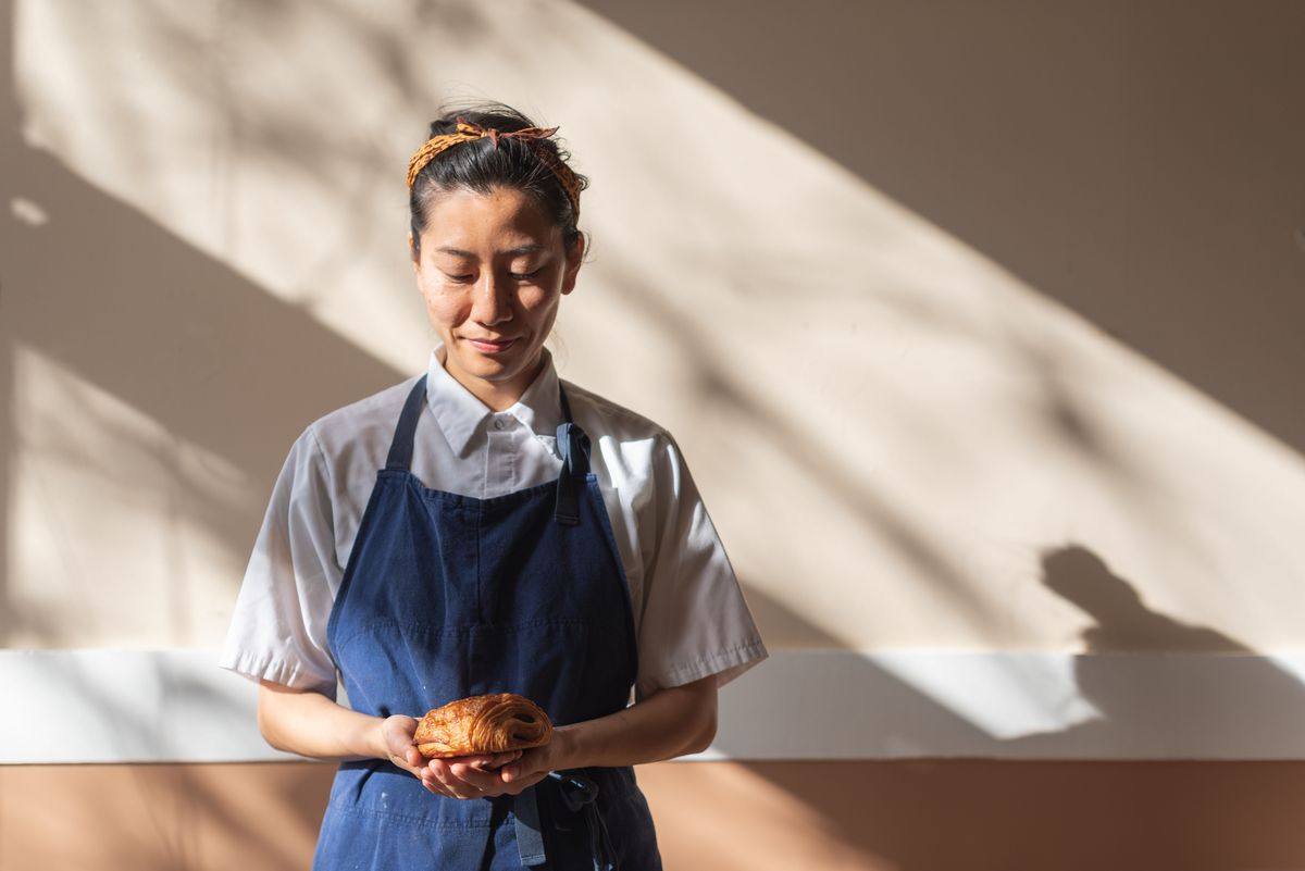 A portrait of Bakers Bench chef Jennifer Yee holding a chocolate croissant.