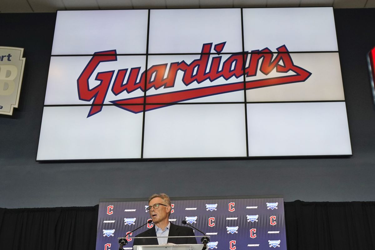 """The word """"Guardians"""" appears on a large screen behind a person standing at a lectern."""