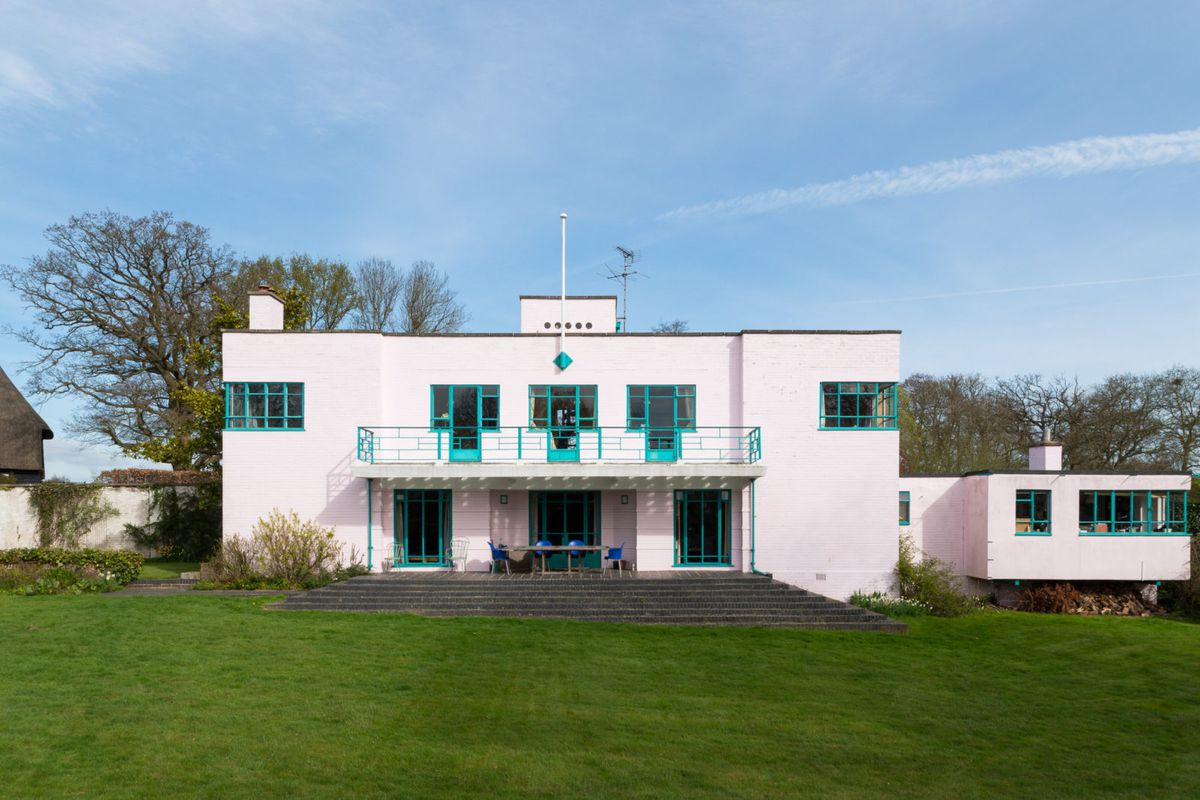 Exterior shot of boxy brick building with pale lavender paint finish and steel-framed windows painted turquoise set on a green field.