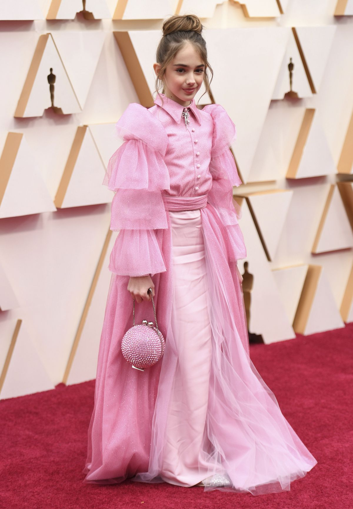 """Ten-year-old Julia Butters, currently featured in """"Once Upon a Time in Hollywood,"""" arrives at the Oscars on Sunday in Los Angeles. Butters collaborated with designer Christian Siriano on her pink gown and accessories."""