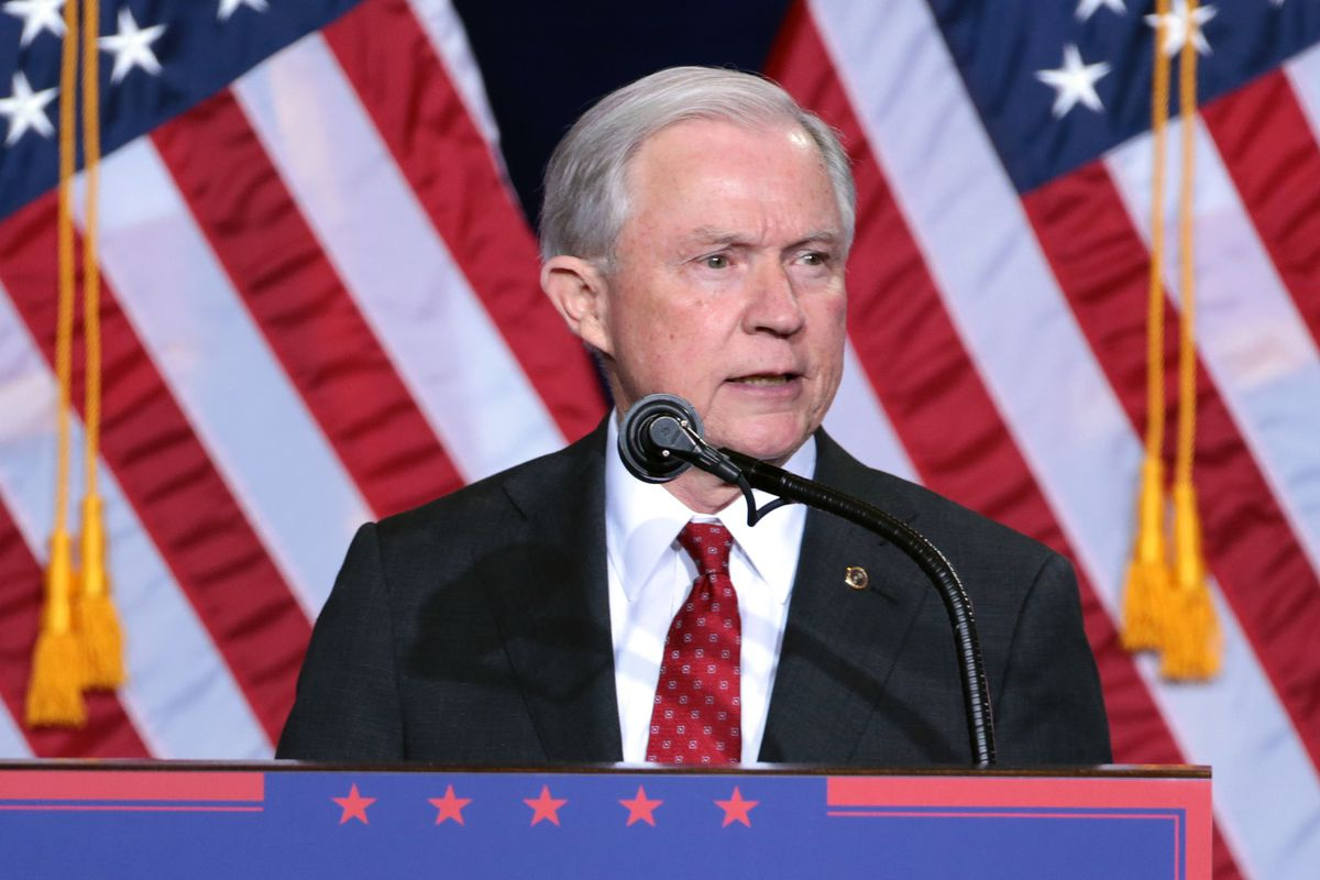 Jeff Sessions at a podium, in front of several American flags.