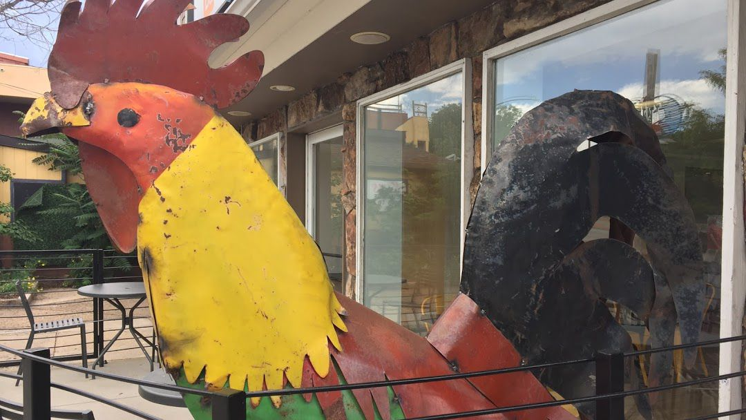 A close-up photo of the upper half of a large and multicolored chicken sculpture on the patio at Chicken on the Hill