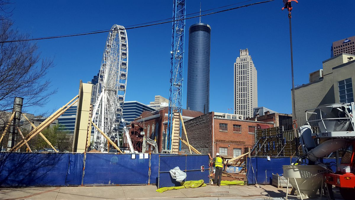 Skyscrapers hover in the background of the construction site, which is wrapped in blue fencing.
